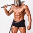 Постер, плакат: Hot warrior in black pants and helmet is holding sword in his sh