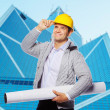 Foreman in hardhat is holding sketch roll — Stock Photo