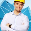 Portrait of happy young foreman in yellow hardhat - Stock Photo