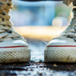 Zoomed white and high girlish gumshoes — Stock Photo #24458481