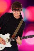 Sahne ışıkları üzerinde sallanan genç müzisyen — Stok fotoğraf