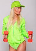 Blondie in coat and panties with red dumbbells — Stock Photo
