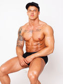 Shy shirtless bodybuilder is sitting on the chair — Stock Photo
