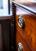 Antique cupboard in front of window — Stockfoto