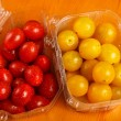 Red and yellow cherry tomatoes in plastic containers — Stock Photo