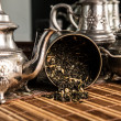 Scattered tea and old teapot — Stock Photo