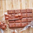 Openned pack of milk chocolate with nuts — Stock Photo #34292059