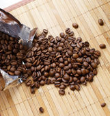 Scattered coffee beans from its pack — Stock Photo