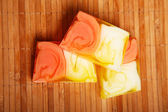 Varicolored pieces of soap on wooden serviette — Stock Photo
