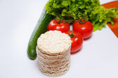 Fresh vegetables and corn crackers on the white background — Stock Photo