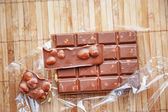 Openned pack of milk chocolate with nuts — Stock Photo