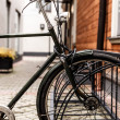 Fragment of a bike parked near a wooden house — Stock Photo #39649857
