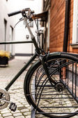 Fragment of a bike parked near a wooden house — Stock Photo