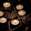 Candles and beaded necklace surrounding a heart — Stock Photo