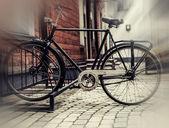 Bici d'epoca parcheggiata nei pressi di una vecchia casa in legno su strada acciottolata — Foto Stock