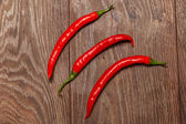 Three chilli peppers on wood — Stock Photo