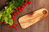 Cutting board and vegetables on a wooden background — Stock Photo