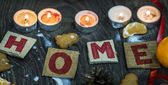 Christmas cardboards saying Home surrounded by candles — Stock Photo