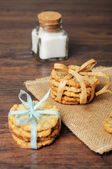 Two stacks of cookies tied with ribbons and a jar — Stock Photo