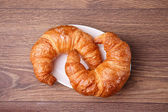 Two croissants on a plate with wooden background — Stock Photo