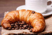 Croissant and coffee beans with a cup on background — Stock Photo