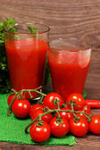 Two glasses of tomato juice on wooden background — Stock Photo