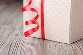 Fragment of a white gift box and a red ribbon — Stockfoto