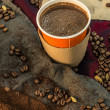 Stock Photo: Coffee in a paper cup with beans and ground coffee