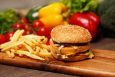 Tasty hamburger and crispy fries on a wooden board — Stock Photo