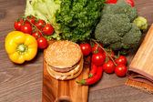 Hamburger and healthy foood on wood — Stock Photo