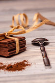 Metal spoon and thin chocolate with a ribbon — Stock Photo