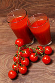 Tomatoes and two glasses on wood — Stockfoto