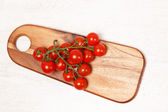 Small tomatoes on a wooden board — Stock fotografie