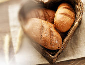 Bread loaves in a heart-shaped basket on a cloth — Stock Photo