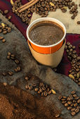 Coffee in a paper cup with beans and ground coffee — Stok fotoğraf