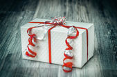 Textured white giftbox with pretty red ribbons — Stock Photo