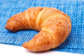 One croissant on blue linen — Foto Stock