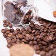 Scattered coffee beans and a glass jar — Stock Photo