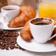 Foto de Stock  : Two cups of coffee with croissants and cup of orange juice