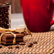 Stock Photo: Some chocolate, coffee beans and red cup