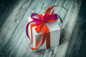 A gift box with red ribbons — Stock Photo