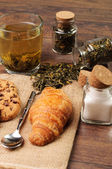 Tiny jars of tea and sugar along with a croissant — 图库照片