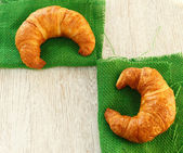 Zwei croissants auf einem grünen leinentuch — Stockfoto