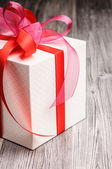 Cube gift box with a shiny red bow — Foto Stock