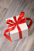 Present in a cube white box with red ribbons — Foto Stock