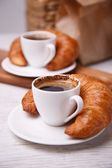 Two cups of coffee and croissants next to them — Stockfoto