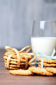 Some cookies with ribbons and a glass of milk — Stock Photo