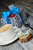A cup of coffee and cookies with a romantic gift box — ストック写真