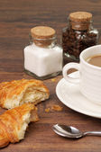 Croissants and crumbs near a cup of coffee — Stock Photo