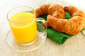 Continental breakfast: croissants and a cup of orange juice — Stock Photo